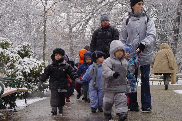 Kindergarden children walking in a snowy park