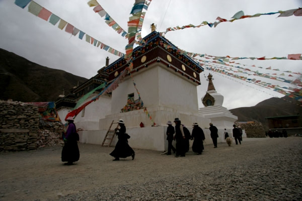 Send picture of People walking around a temple complex in Tibet from China as a free postcard