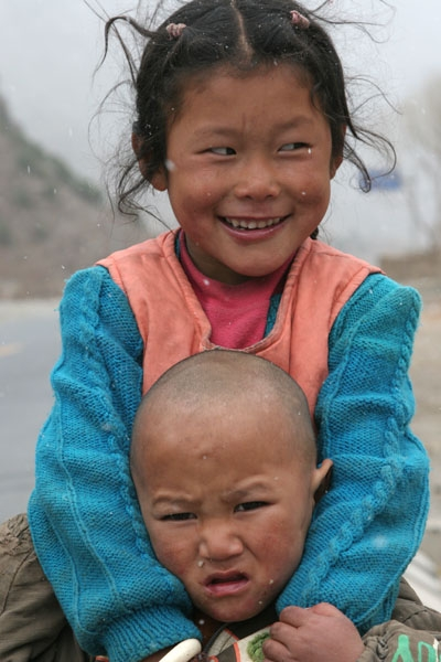 Send picture of Sister and brother posing outside Jyekundo town in Tibet from China as a free postcard