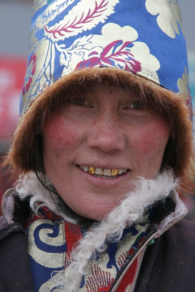 Send picture of Tibetan woman from Jyekundo with typical hood and golden teeth from China as a free postcard