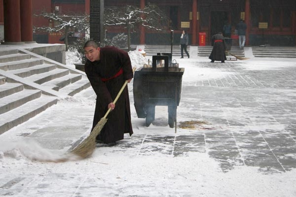 Monk clearing snow in Peking