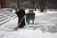 Foto di Monk clearing snow in Peking - China