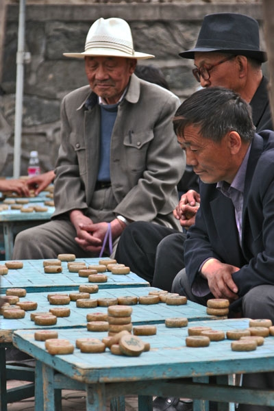 Send picture of Men playing a board game in Xining from China as a free postcard