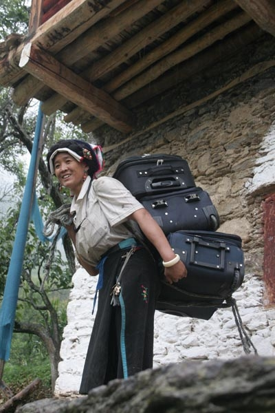 Send picture of Tibetan woman working in a Jiaju guesthouse from China as a free postcard