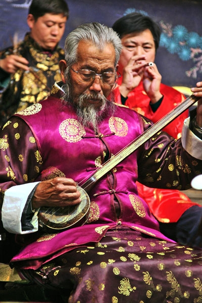 Send picture of Man performing with a traditional Naxi orchestra in Lijiang from China as a free postcard
