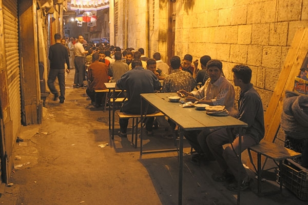 Send picture of Men getting ready to eat in a Cairo street after sunset during Ramadan from Egypt as a free postcard