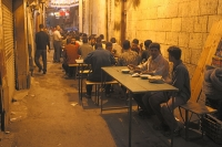 Foto di Men getting ready to eat in a Cairo street after sunset during Ramadan - Egypt