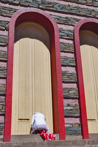 Send picture of Woman praying at the door of an orthodox church in Asmara from Eritrea as a free postcard