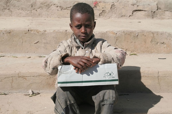 Send picture of A boy selling condoms and medicine from his little box to support the household from Ethiopia as a free postcard
