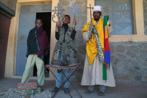 Send picture of A priest and his helpers earn their living from entrance fees and tips from visitors from Ethiopia as a free postcard
