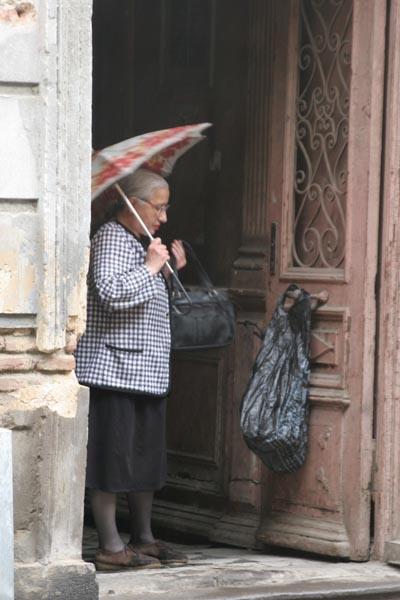 Envoyer photo de Woman preparing for the rainy Tblisi streets de Géorgie comme carte postale électronique