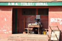 Foto van Toilet supervisor collecting a small fee - Ghana