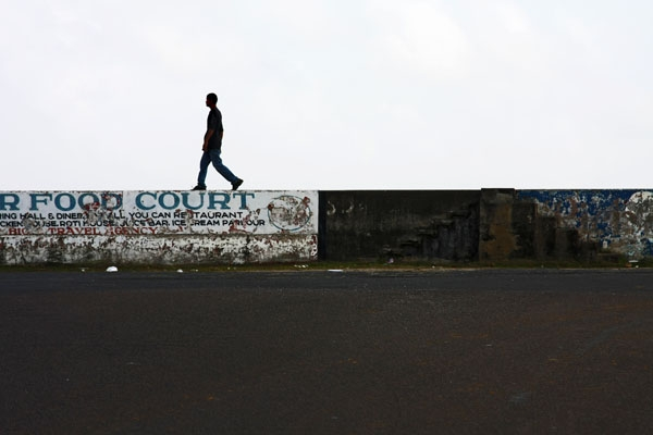 Send picture of Man walking on the sea wall in Georgetown from Guyana as a free postcard
