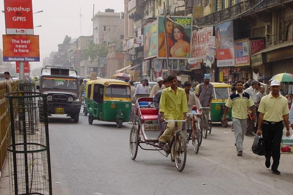 Send picture of Rickshaws, people, cyclists and cars in Delhi from India as a free postcard