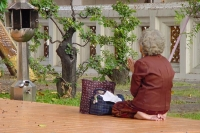 Picture of Woman praying at a Buddhist temple - Laos