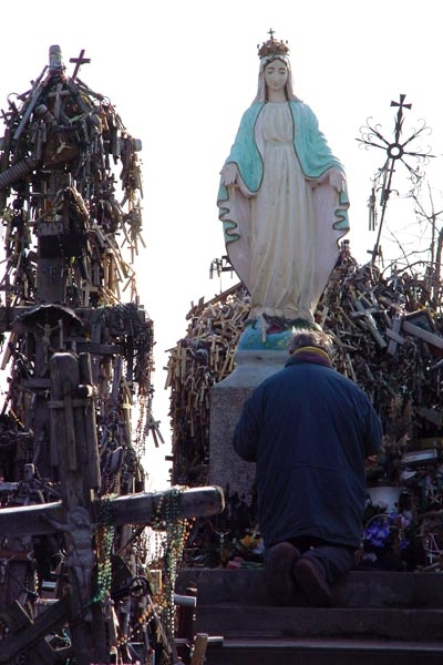 Send picture of Man praying at the Hill of Crosses in the vicinity of Siauliai from Lithuania as a free postcard