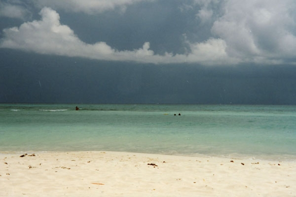 Send picture of Clear waters of Playa del Carmen and a threatening sky from Mexico as a free postcard