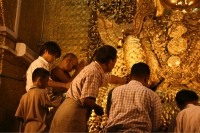 Photo de Men putting gold leaves on a Buddha statue - Myanmar (Burma)