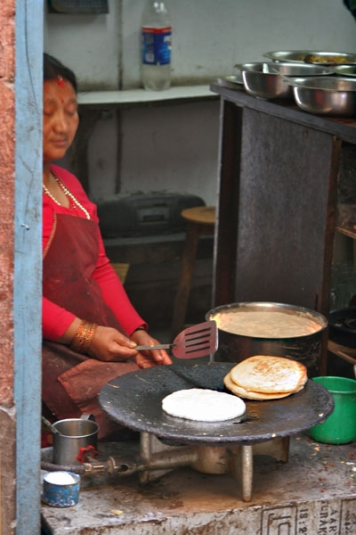 Send picture of Woman cooking in a Nepali street kitchen from Nepal as a free postcard