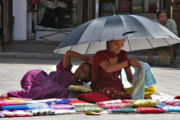 Send picture of Clothes vendors sitting and lying under a parasol from Nepal as a free postcard