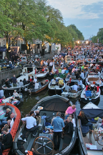 Send picture of Boat owners at a popular concert on a canal in Amsterdam from Netherlands as a free postcard
