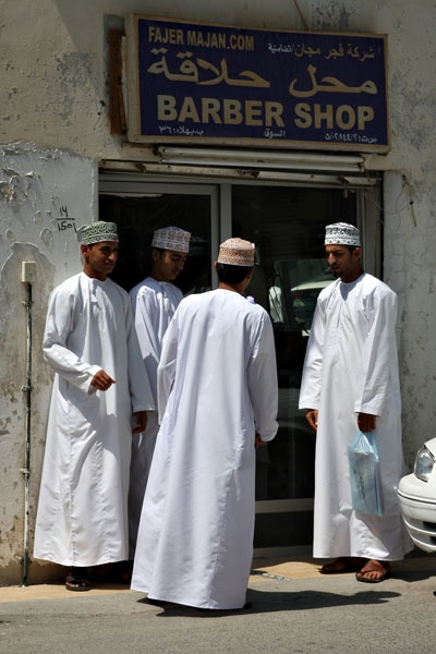 Send picture of Omani men in front of a barber shop from Oman as a free postcard