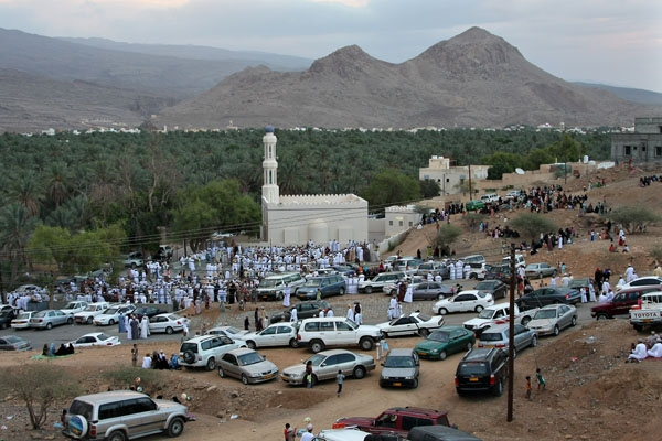 Send picture of People and cars around a mosque in Al Hamra at Eid from Oman as a free postcard