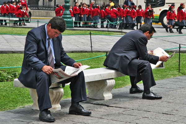 Businessmen reading newspapers in Lima