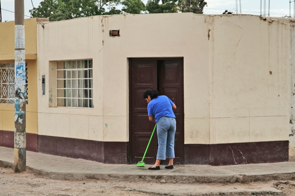 Stuur foto van Woman cleaning in front of her house in Nazca van Peru als een gratis kaart