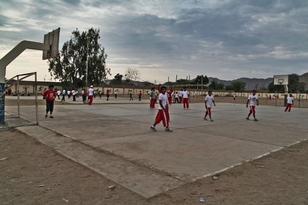 Send picture of Students playing football in a school in Nazca from Peru as a free postcard