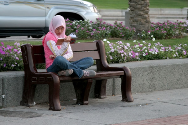 Send picture of Girl reading by the corniche in Doha from Qatar as a free postcard