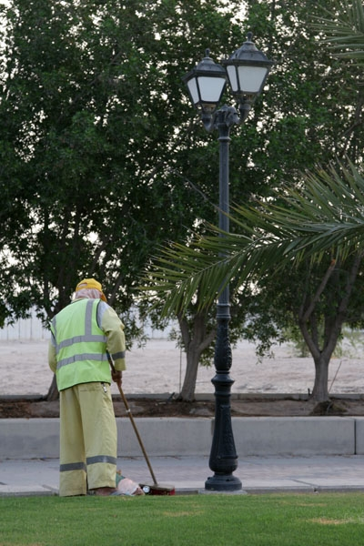 Send picture of Man cleaning a Doha park from Qatar as a free postcard