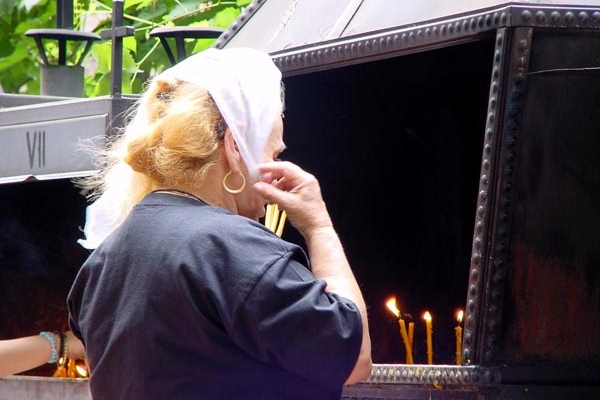 Woman lighting prayer candles