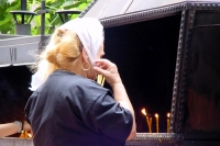 Picture of Woman lighting prayer candles - Romania