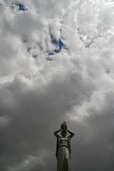 Send picture of Clouds over a statue in Madrid Botanical Garden from Spain as a free postcard