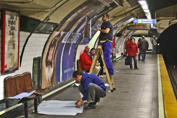 Send picture of Men putting up posters at a subway station in Madrid from Spain as a free postcard