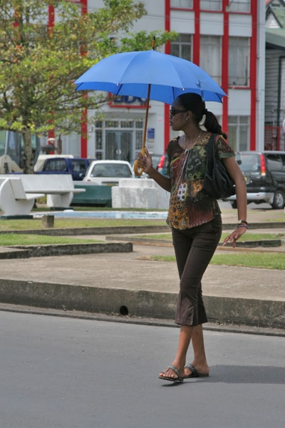 Send picture of Woman carrying a parasol in Paramaribo from Surinam as a free postcard