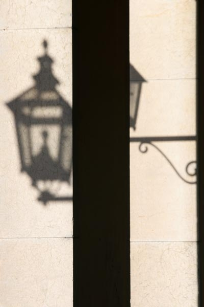 Street lamp casting shadow on a wall
