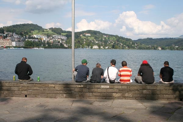Send picture of Young people sitting by Reuss River in Lucerne from Switzerland as a free postcard