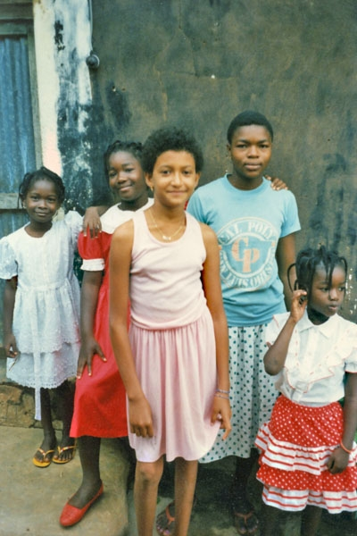 Send picture of Girls posing in front of a house from Togo as a free postcard