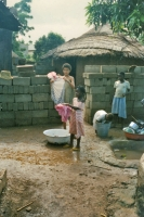 Picture of Girls doing laundry outside a house in Togo - Togo