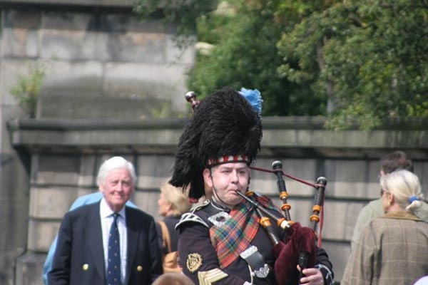 Send picture of Scottish man playing bagpipe from United Kingdom as a free postcard