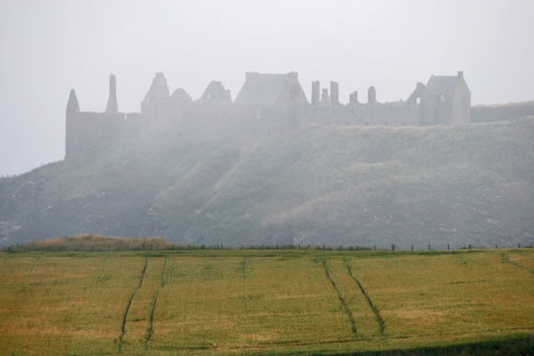 A foggy day in Scotland with the contours of Dunnottar Castle