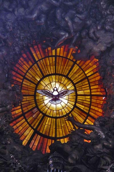 Envoyer photo de A yellow window in St. Peter's cathedral featuring the Holy Spirit as a dove surrounded by 12 rays, symbolising the apostles  de Cité du Vatican comme carte postale électronique