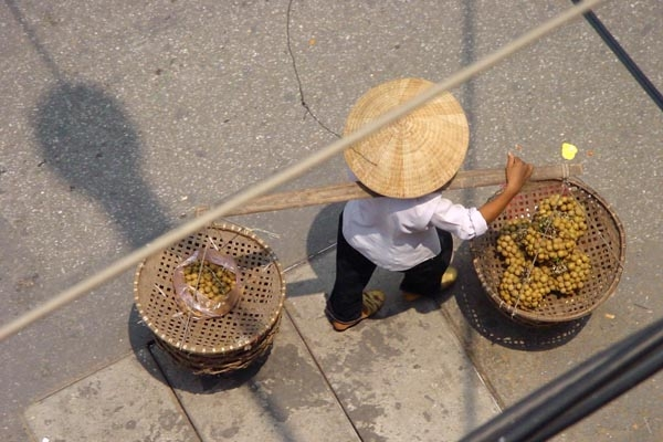Send picture of Woman carrying fruit in her baskets from Vietnam as a free postcard