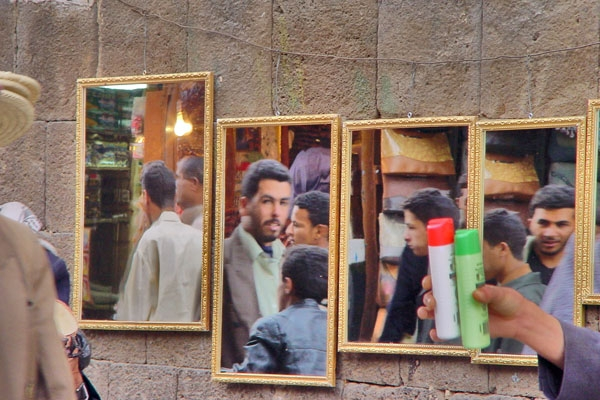 People in the souk of Sanaa reflected in mirrors